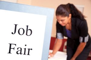 foreground Job Fair sign, background a person signs up