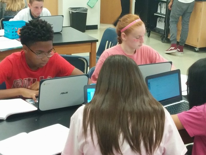 A group of middle school students intently focused on their Chromebooks in class.