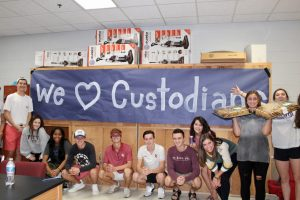 "Edmond Memorial students hold banner saying, ""We love Custodians."""