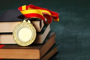 Gold medal draped over a stack of books