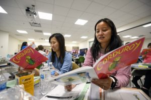 Parents look at books provided during an early birds program