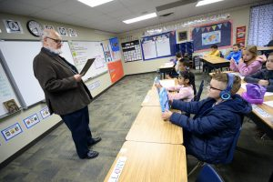 Dr. Dennis Canfield, a substitute teacher, reads over the instructions for the day at Northern Hills Elementary