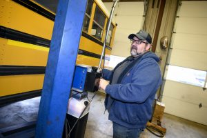 Bus transportation supervisor Garrett Henson works on a bus