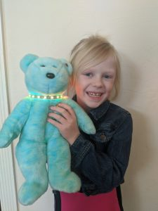 Student holds Teddycare (a stuffed bear with a light up necklace use to detect a child's illness).