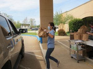 Child Nutrition Worker Carries sack lunches to a car full of hungry kids