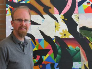 Keith Pautler stands in front of a colorful tiger mosiac at Central Middle School