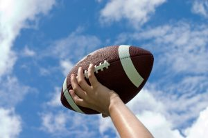 Teen boy catches football in air against blue sky