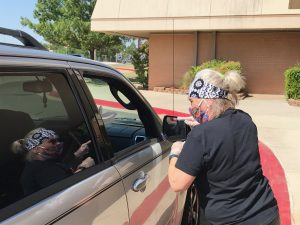 Child Nutrition Worker Delivers Meals to Person Waiting in their car