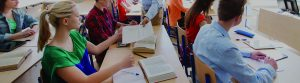 High School students pass a book to each other