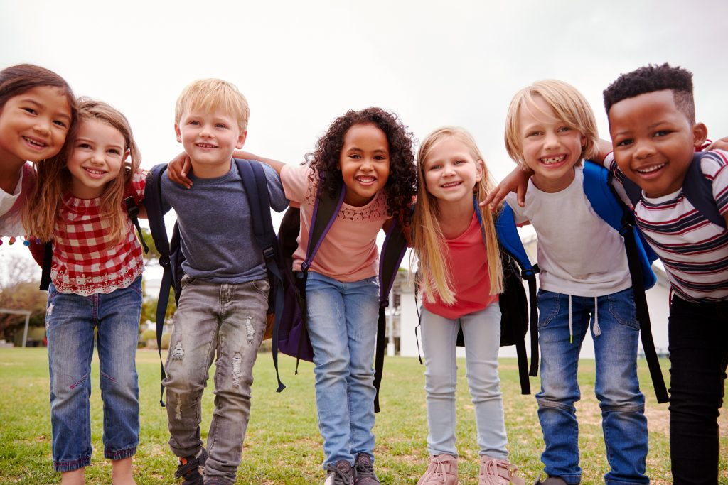 Group of children carrying backpacks on the playground